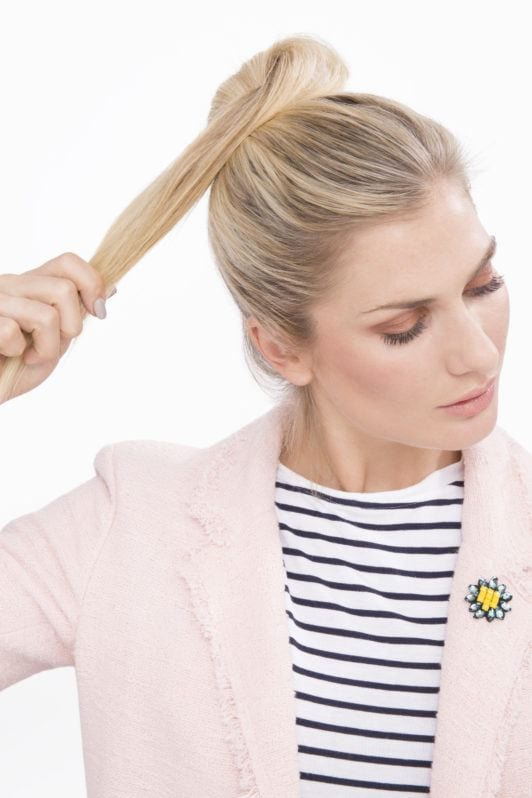Messy bun: Woman with blonde hair wrapping her ponytail into a bun