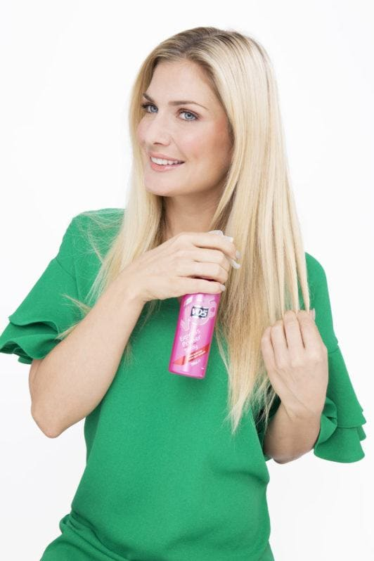 woman with long blonde hair spraying the VO5 primer spray into her hair