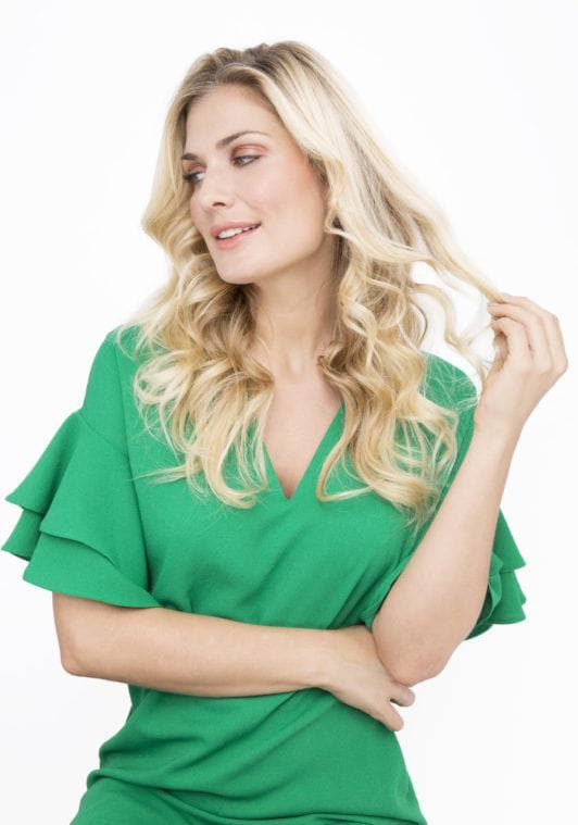 woman with long blonde hair in undone waves wearing a green dress