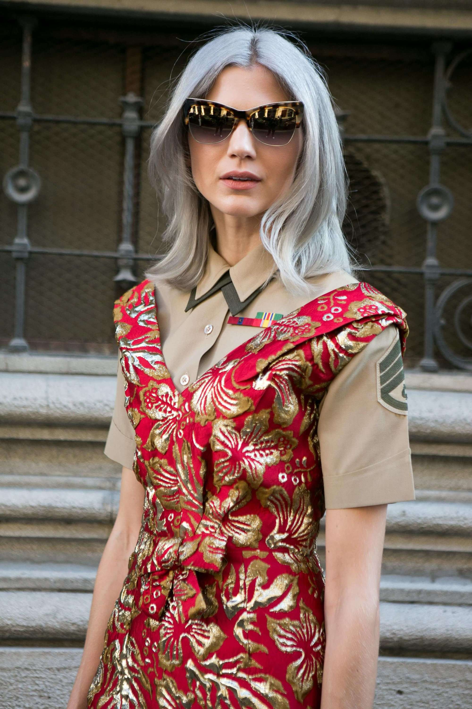 street style blogger at milan fashion week wearing a red floral dress with grey medium length hair