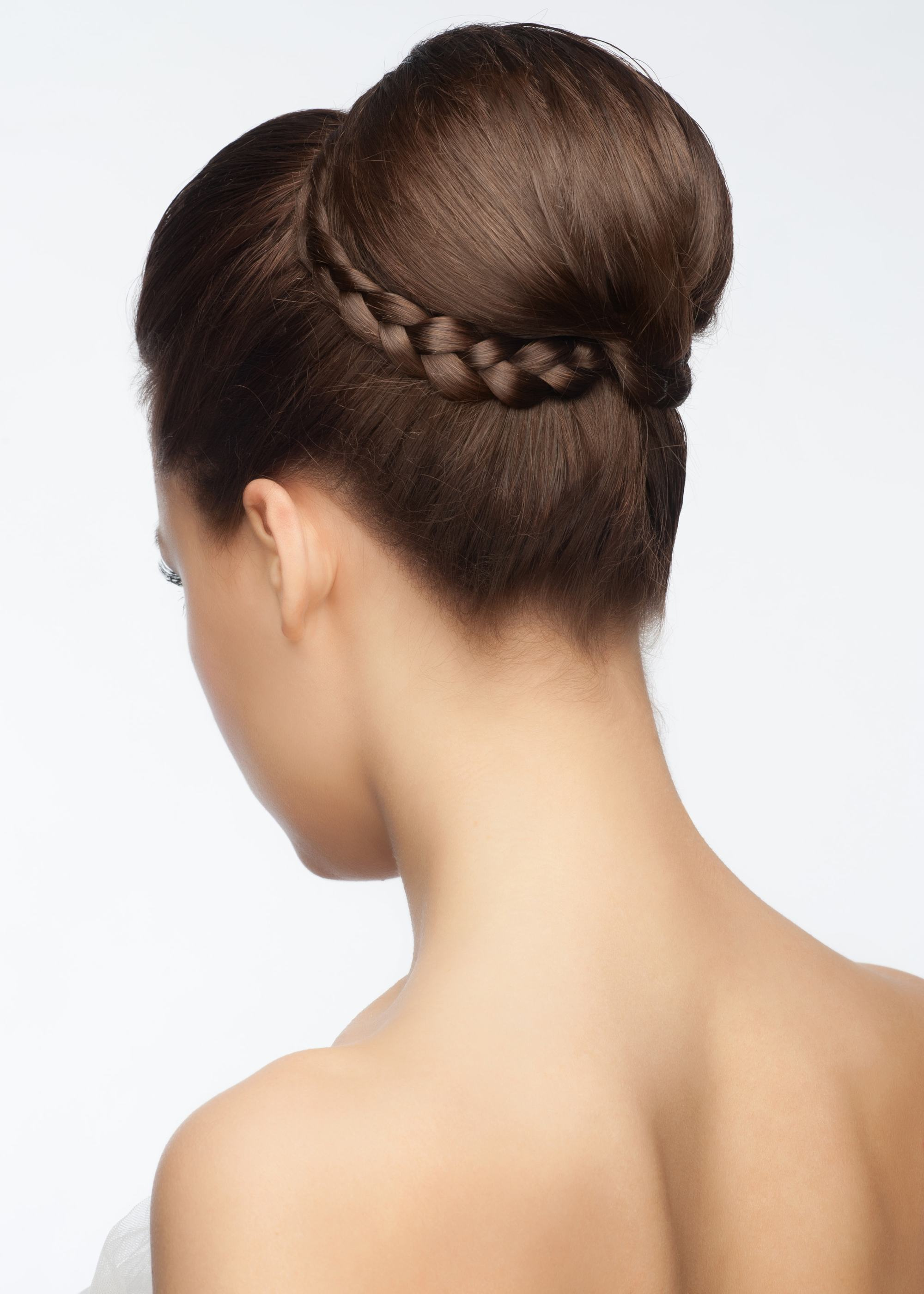 Brown hair in high chignon hairstyle wrapped with a braid