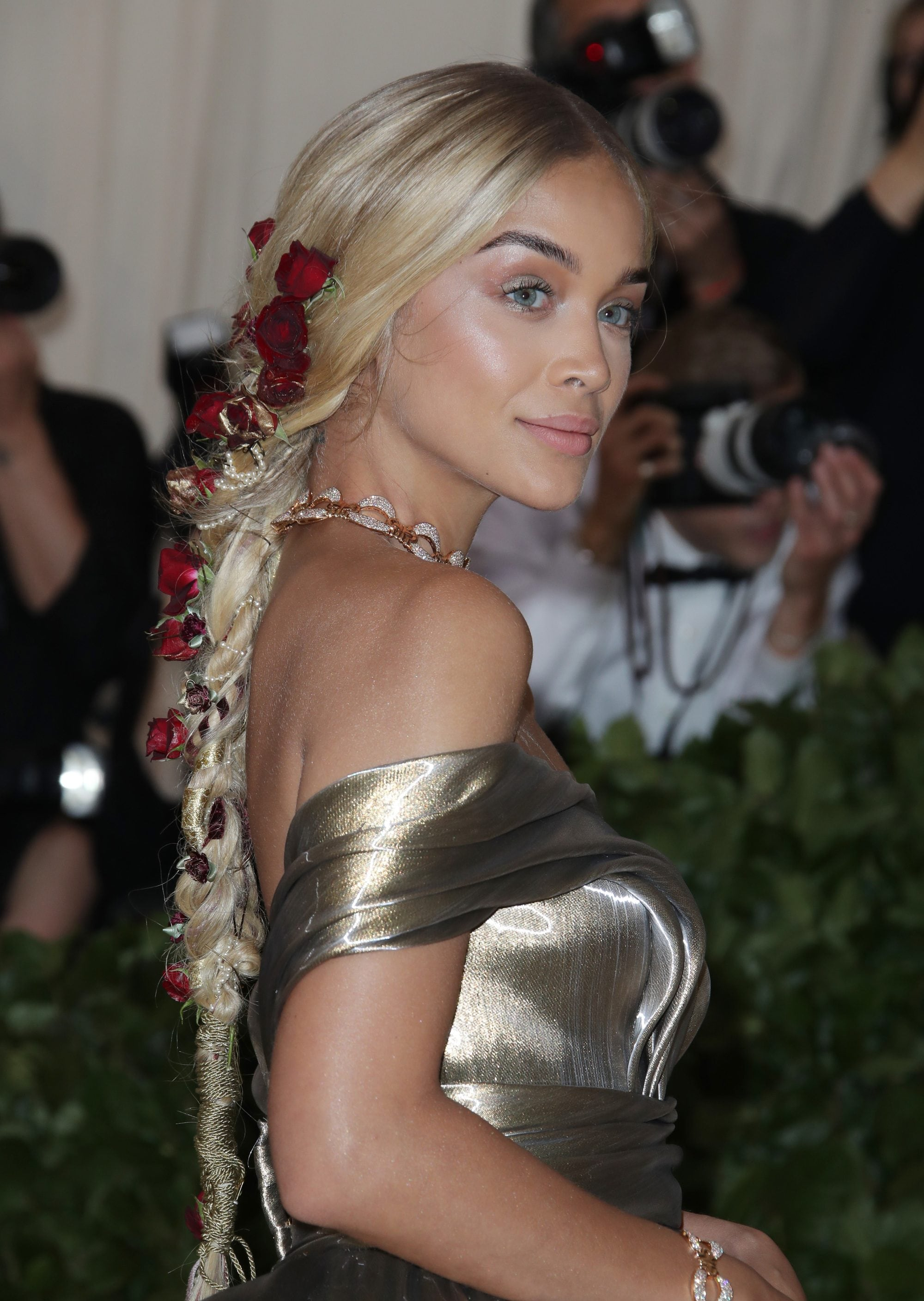 close up shot of jasmine sanders with braided low ponytail with red flowers weaved into it, wearing golden gown and posing on the 2018 met gala red carpet