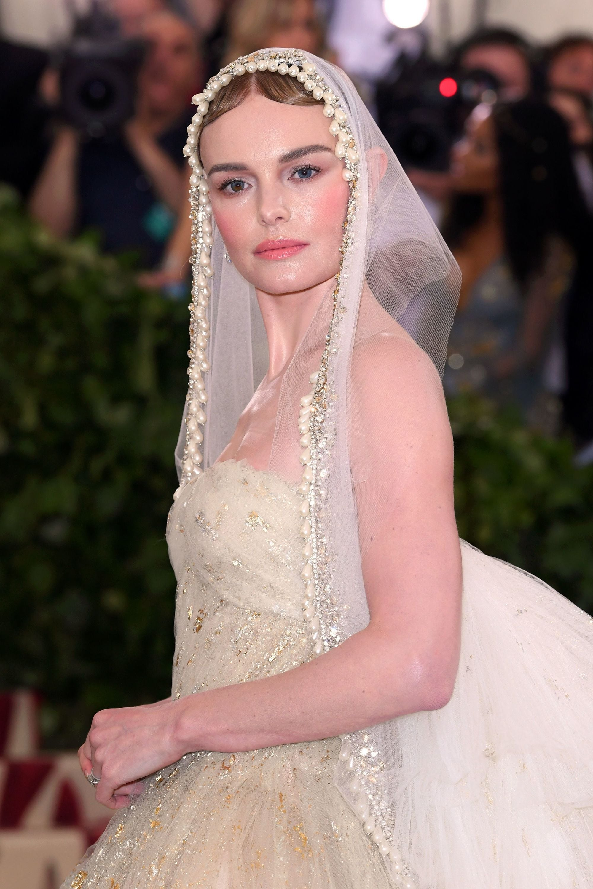 close up shot of kate bosworth with finger waves bun hairstyle and pearl veil hair accessory, wearing all white and posing on the 2018 met gala red carpet