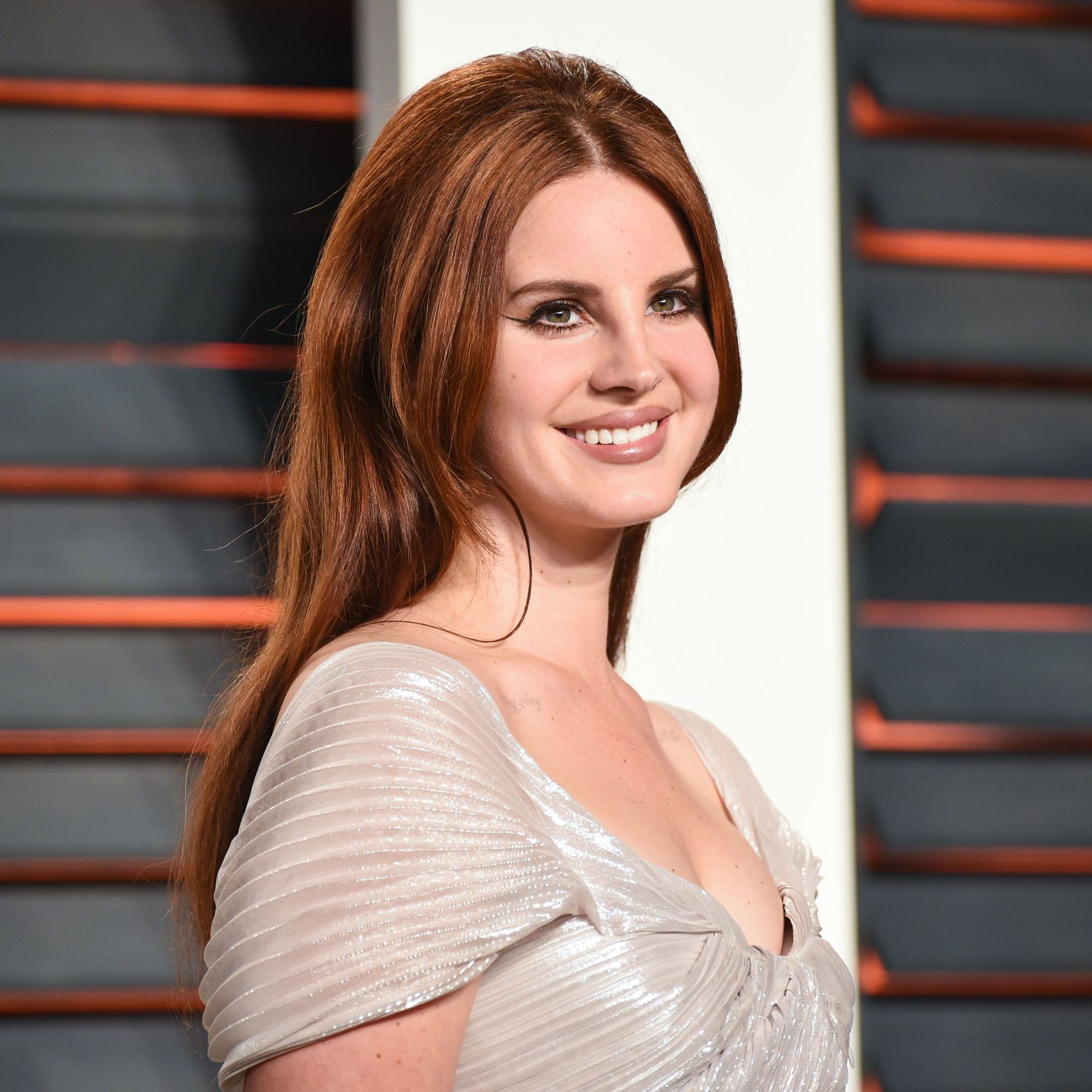 singer lana del rey on the red carpet with fiery auburn hair in a half up bouffant