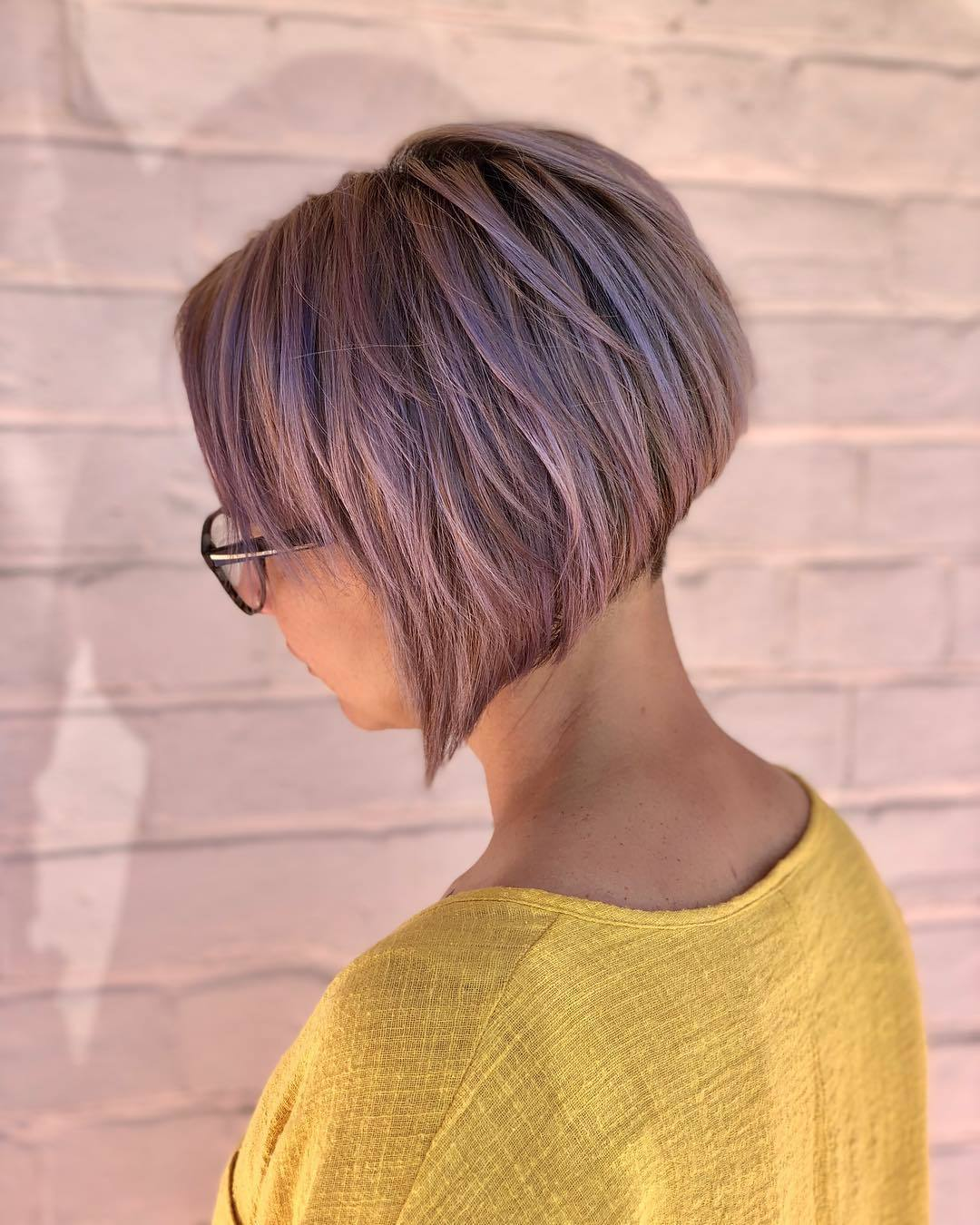 Graduated bob hairstyles: Woman with short lilac graduated bob hairstyle wearing yellow and posing outside