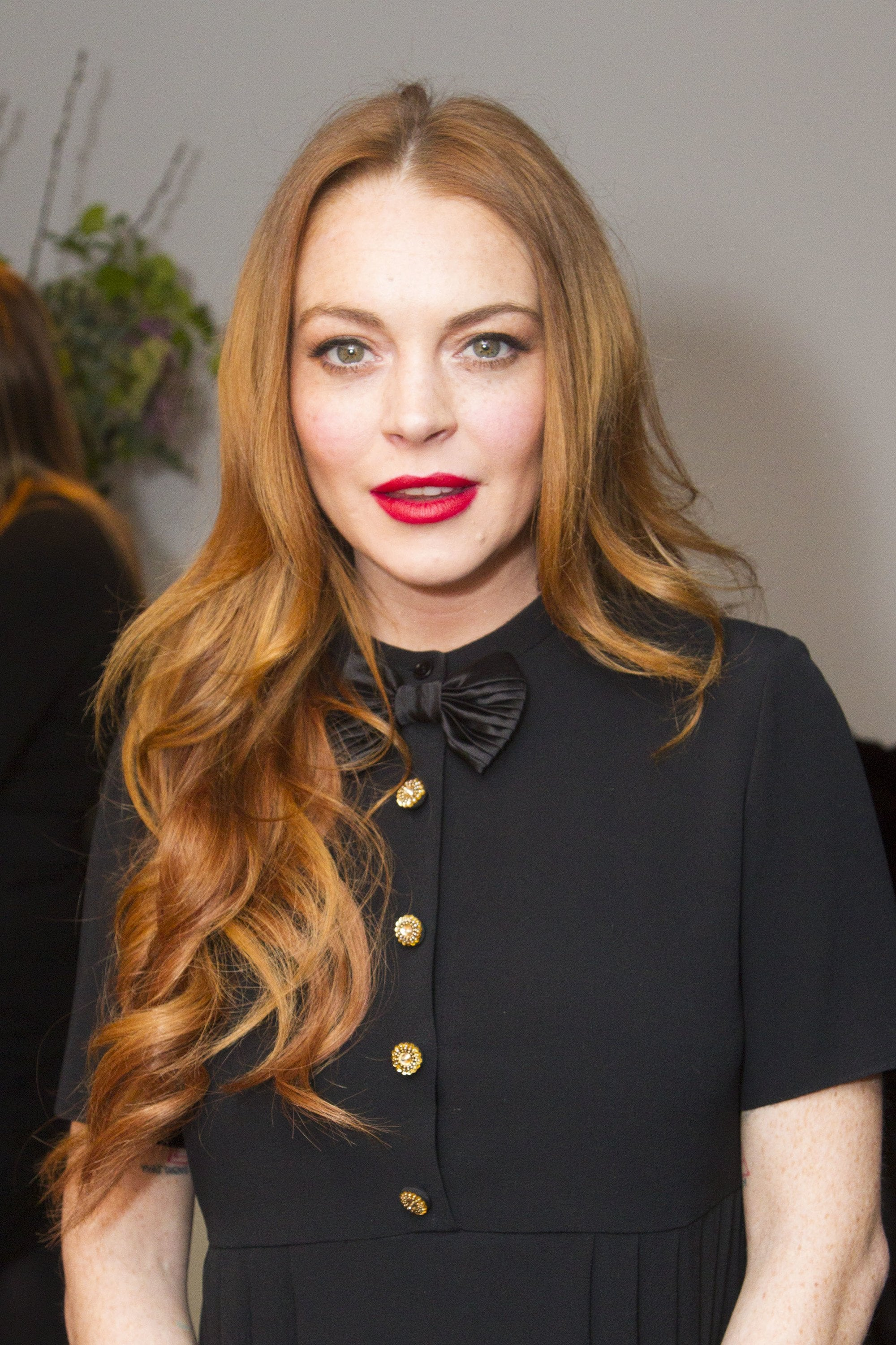 lindsay lohan with her red hair in a sideswept curly style