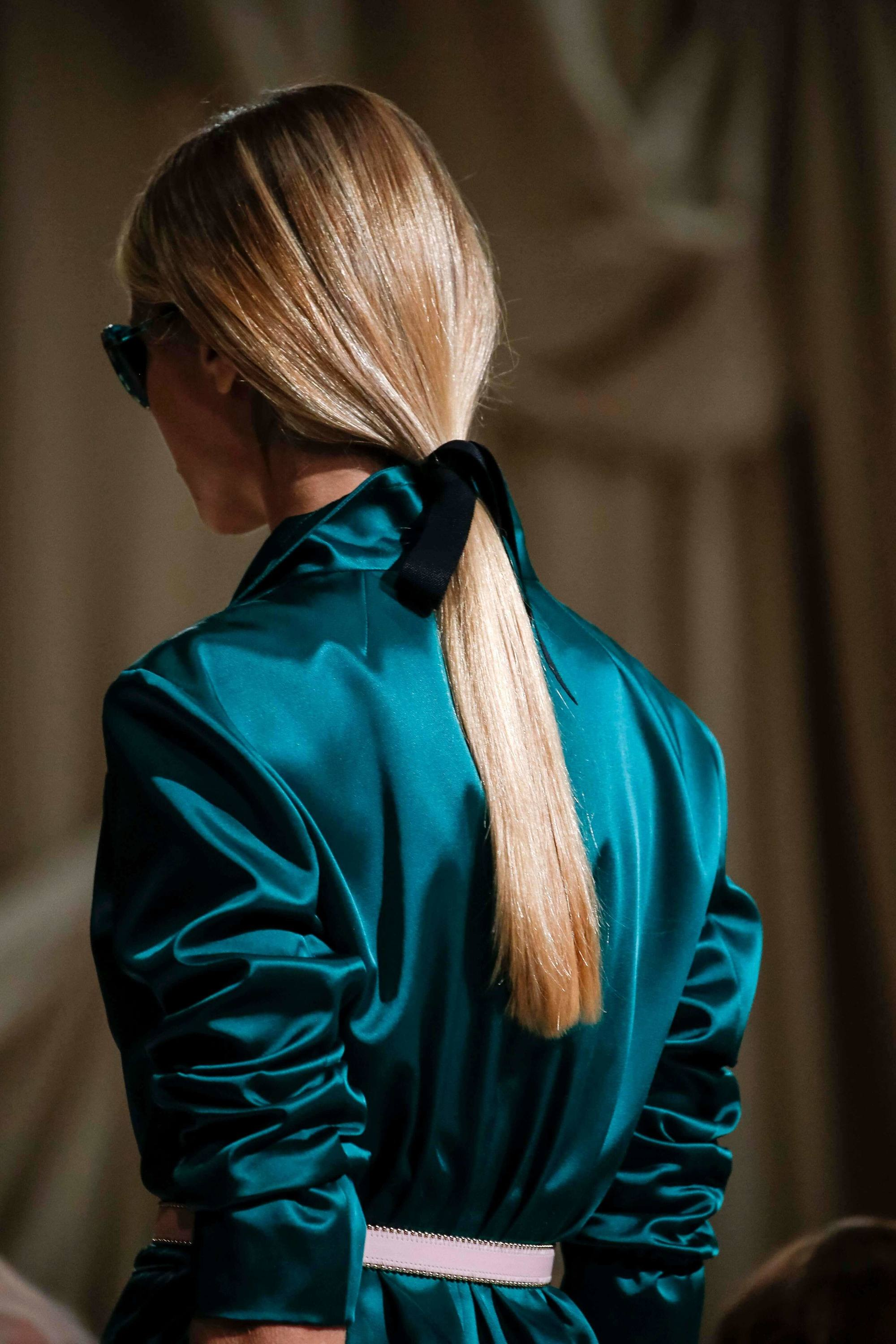 blonde model on the runway with a low ponytail secured with a ribbon - how to get straight hair tutorial