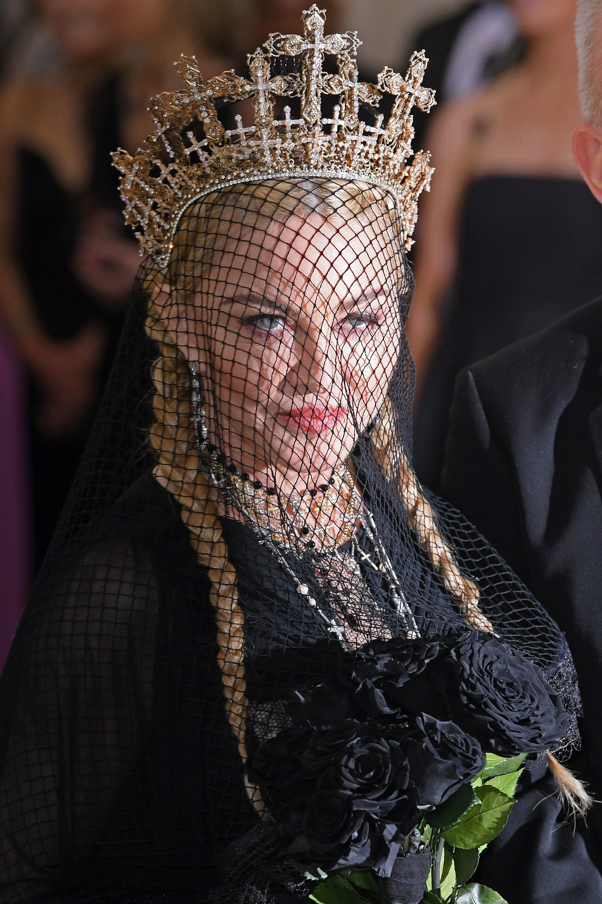 close up shot of madonna with pigtails and netted veil, wearing a crown and all black gown and posing on the 2018 met gala red carpet