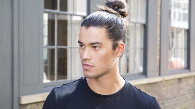 Man bun tutorial brunette man looking away from camera in street
