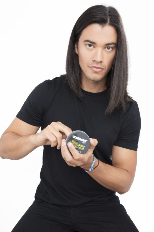 Dark haired man scooping product to his dark brown hair