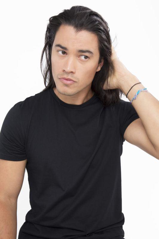 Dark haired man applying product to his dark brown hair