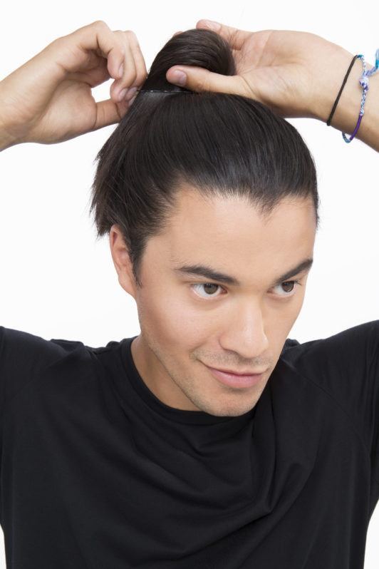 Dark haired man tying his dark brown hair