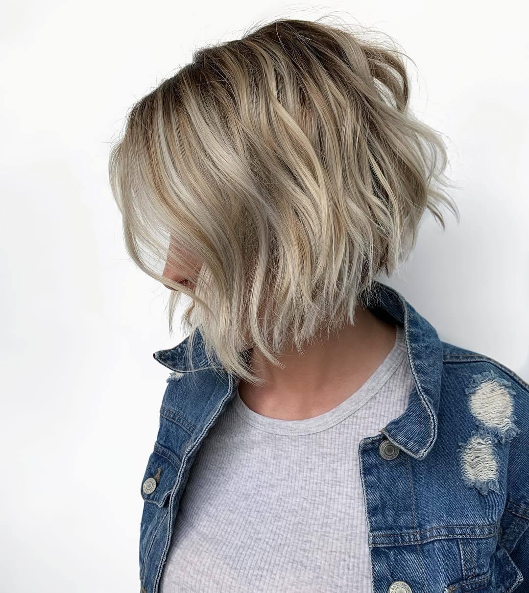 Woman with ash blonde wavy graduated bob, wearing grey top and denim in studio