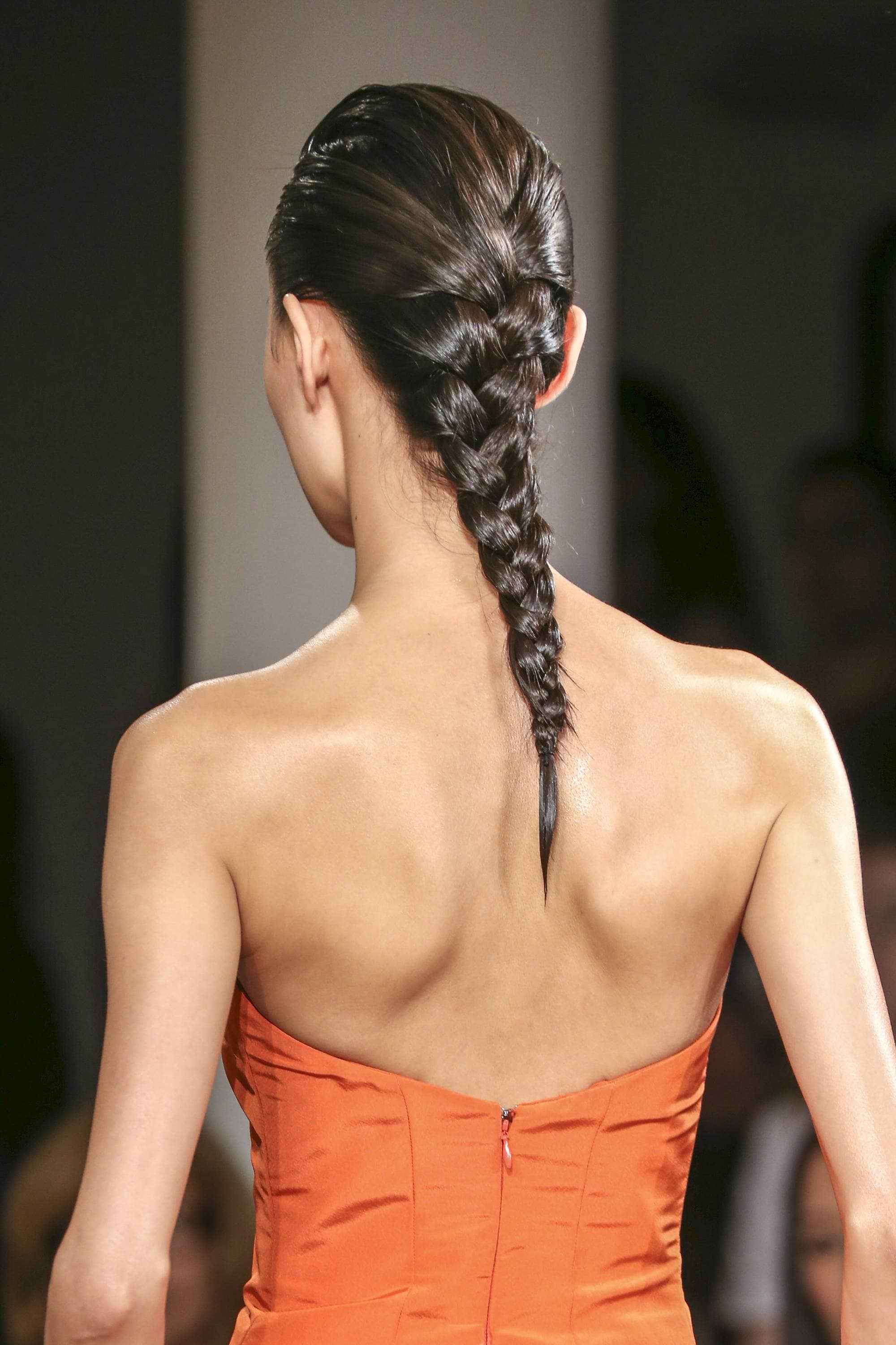 peter som model wearing an orange dress with her brunette hair in a french plait
