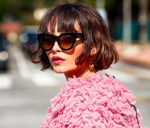 Layered bob: Photo of model/influencer Taylor Lashae with a brunette wavy bob with a fringe, wearing sunglasses and a shaggy pink jacket