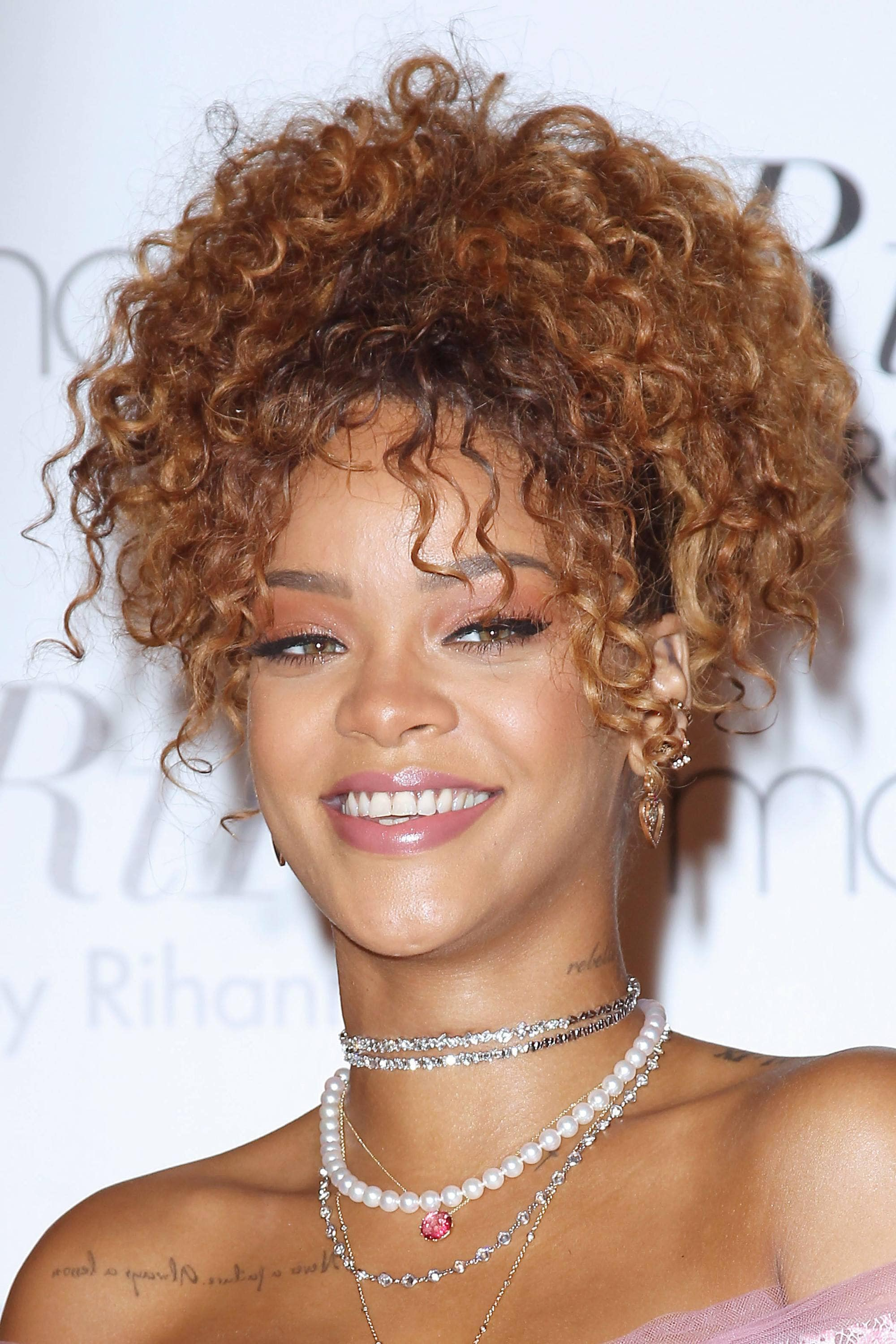 rihanna on the red carpet with an auburn pineapple updo