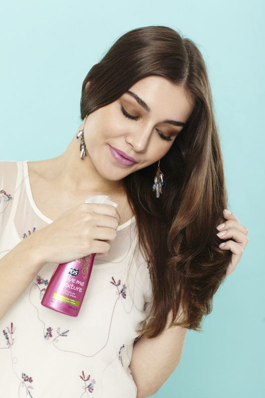 beach waves hair: woman with long brunette hair spritzing her hair with a tousle style spray