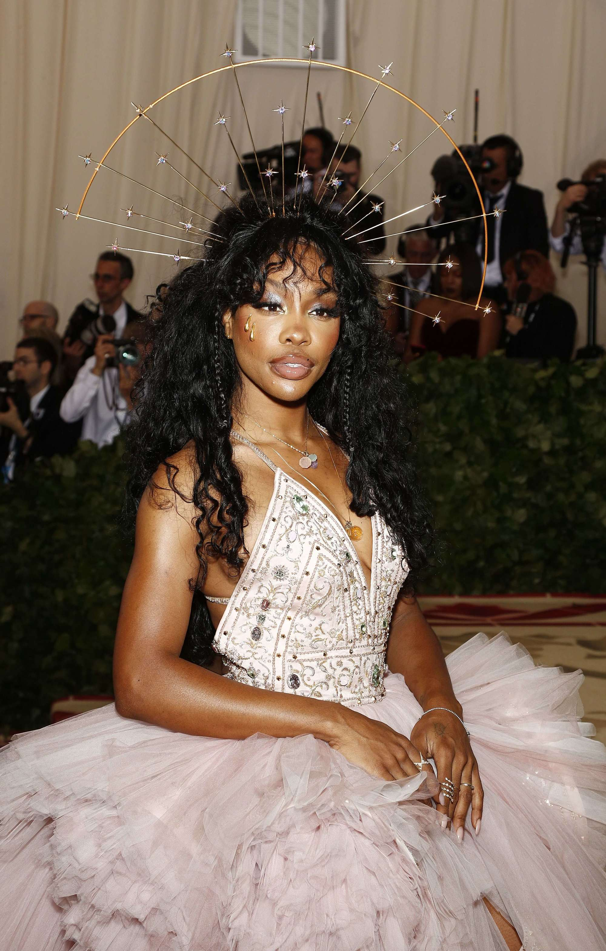 close up shot of SZA with wavy curly hair with hidden braids in it, and a halo hair accessory wearing pink ballgown and posing on the 2018 met gala red carpet