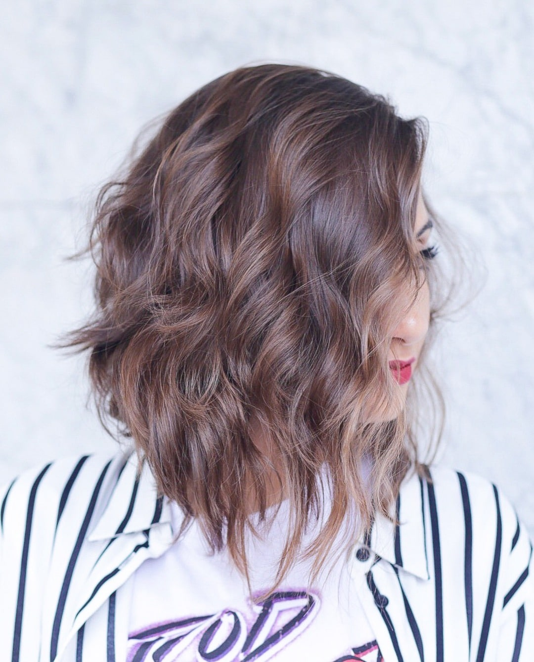 Graduated bob: Woman with chestnut brown long bob with graduated layers at the back posing in a studio