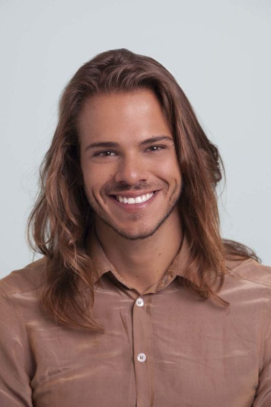 a long hair mman smiling to the camera