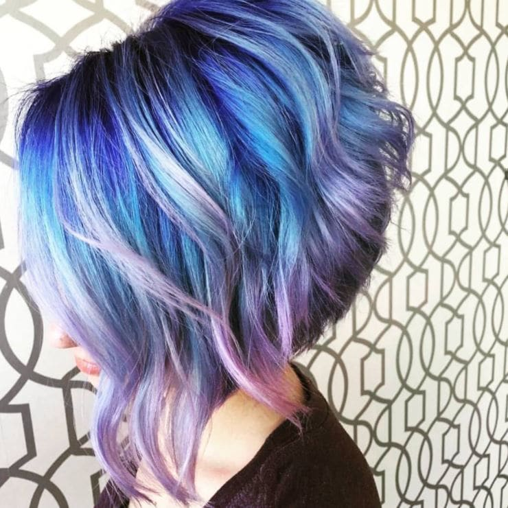 Graduated bob with waves in violet geode hue from side view
