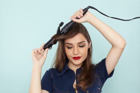 beach waves hair: model with curling wand creating waves