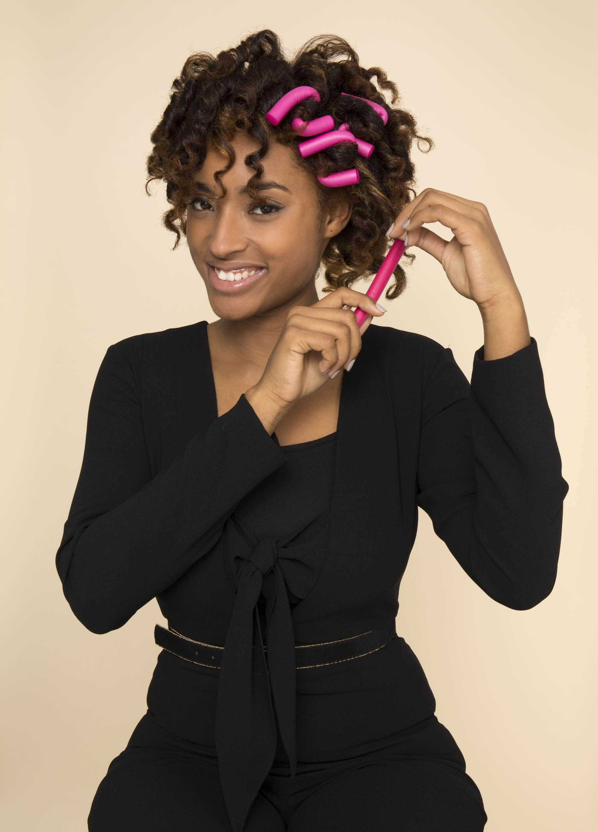black model curling her hair with pink flexi rods