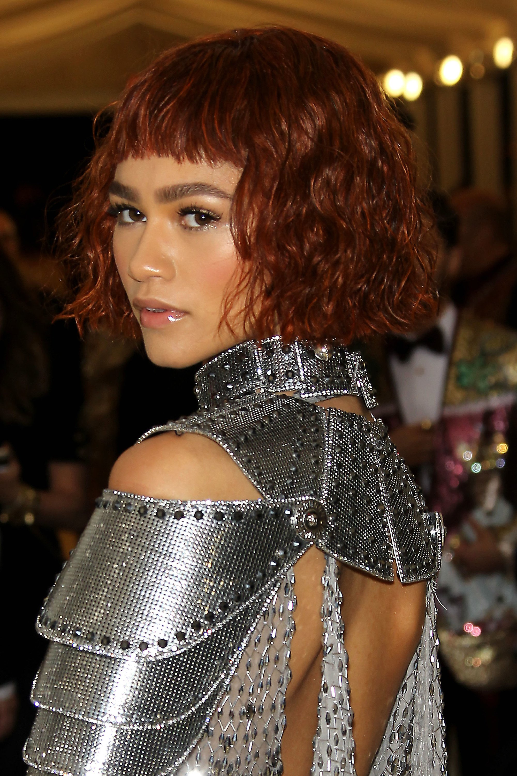 close up shot of zendaya with micro fringe and bob, wearing silver plated dress and posing on the 2018 met gala red carpet