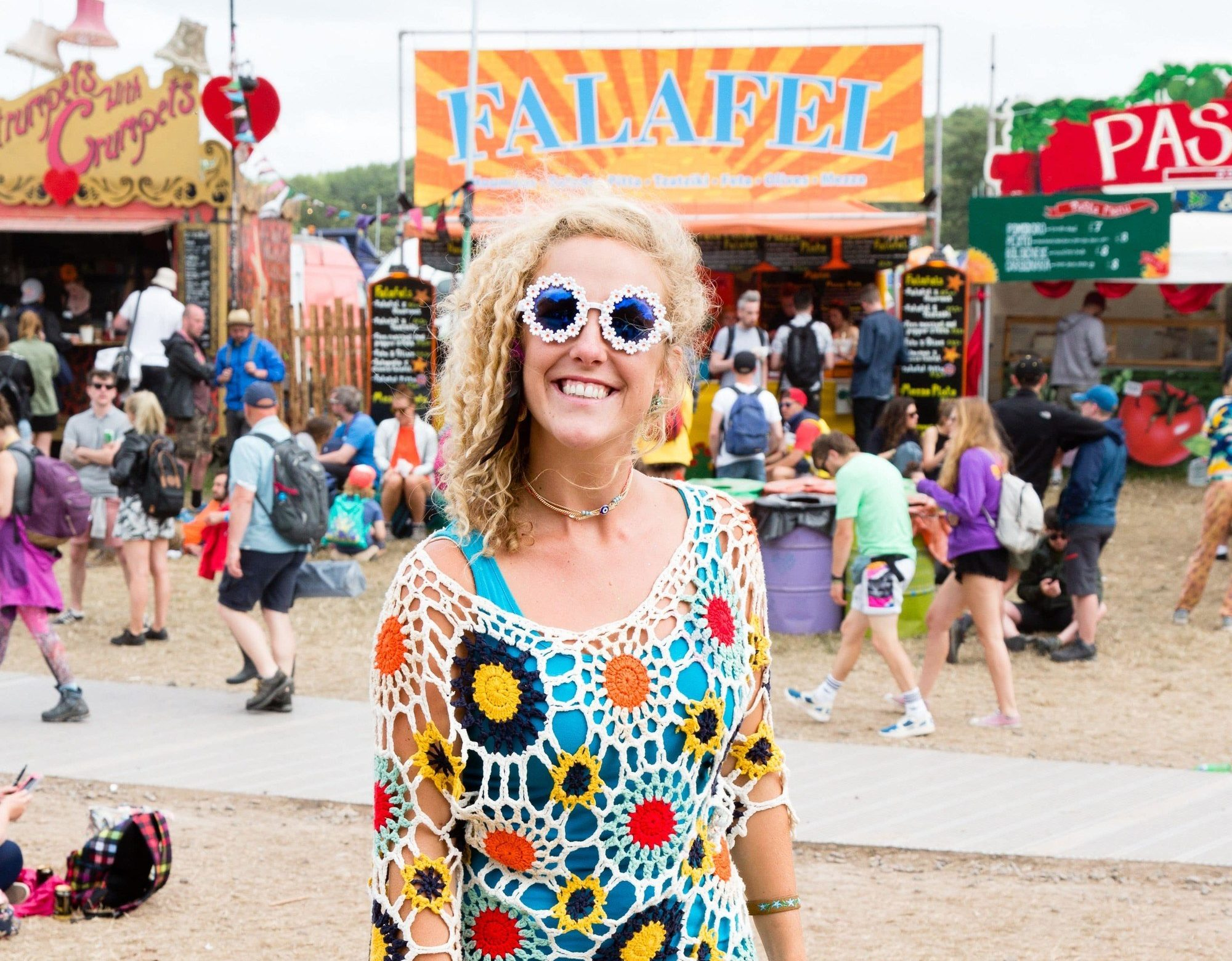 woman at glastonbury with spiral curls 80s hairstyle wearing blue outfit