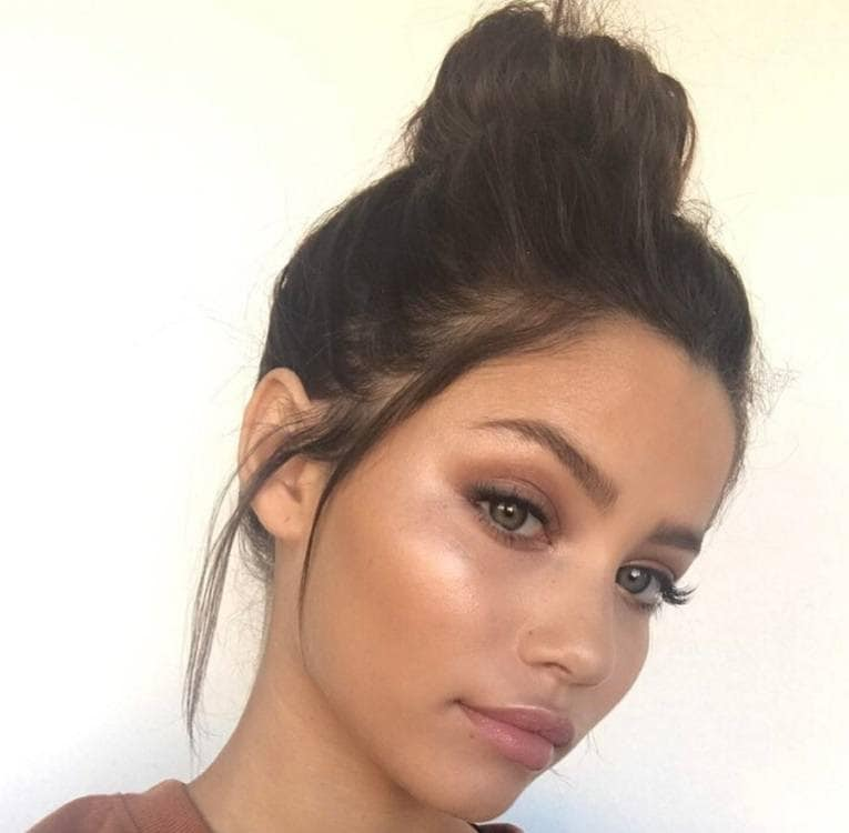 hairstyles for greasy hair: woman with messy bun hairstyle