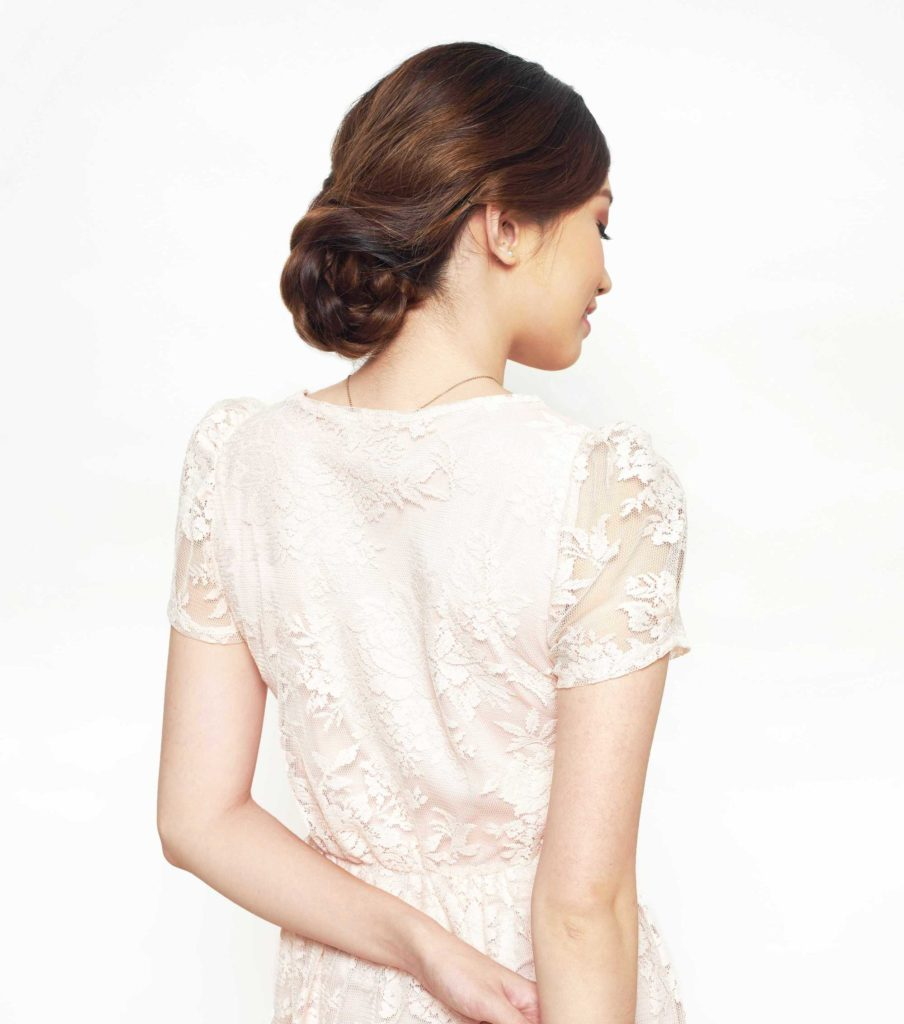 Easy prom hairstyles: Back shot of a model with chestnut brown hair styled into a low braided updo, wearing a white lace dress and posing in a studio.