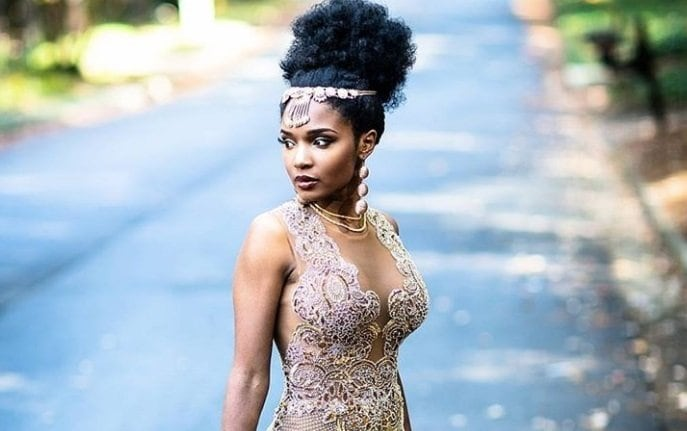 Curly wedding hair: Close up shot of woman with afro hair styled into a pineapple bun updo, wearing bridal clothing and posing outside