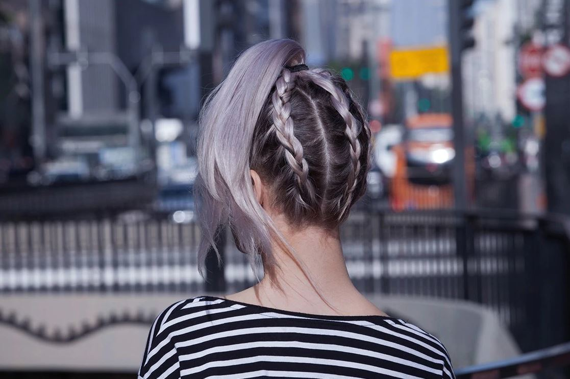 Festival hair: back view of woman with grey silver ombre hair style din a upside down braided ponytail on london street