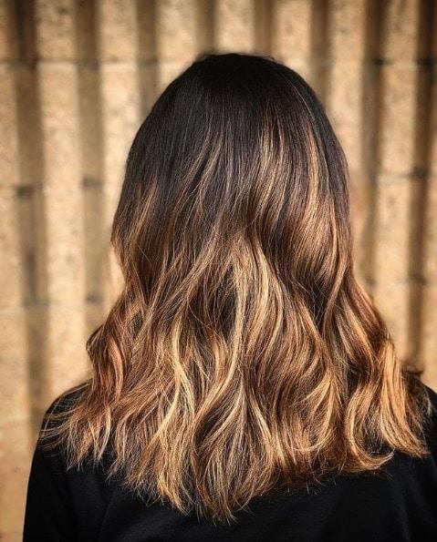 Caramel highlights: Close up dark brunette caramel babylights on shoulder-length wavy hair