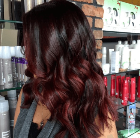 chocolate cherry hair colour: salon shot of women with dark chocolate hair with cherry highlights
