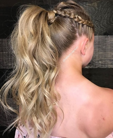 Curly prom hairstyles: Back view of a blonde girl with her hair in a braided curly ponytail