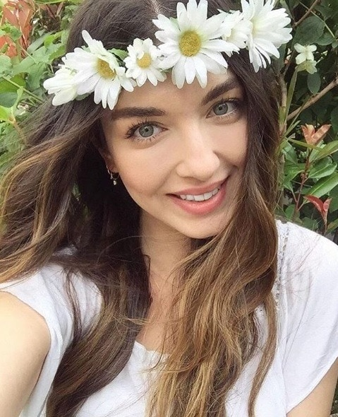 Boho hairstyles: Selfie of a brunette girl with wavy hair wearing a boho daisy chain crown headband