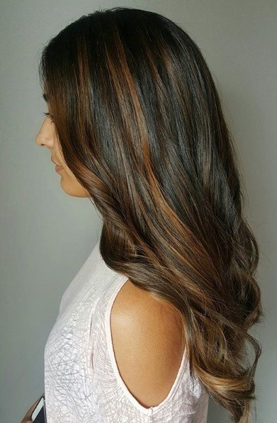 Caramel highlights: Side view of a woman with long dark caramel highlighted hair, loosely curled at the ends