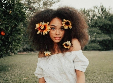 black model with flowers in her afro hair