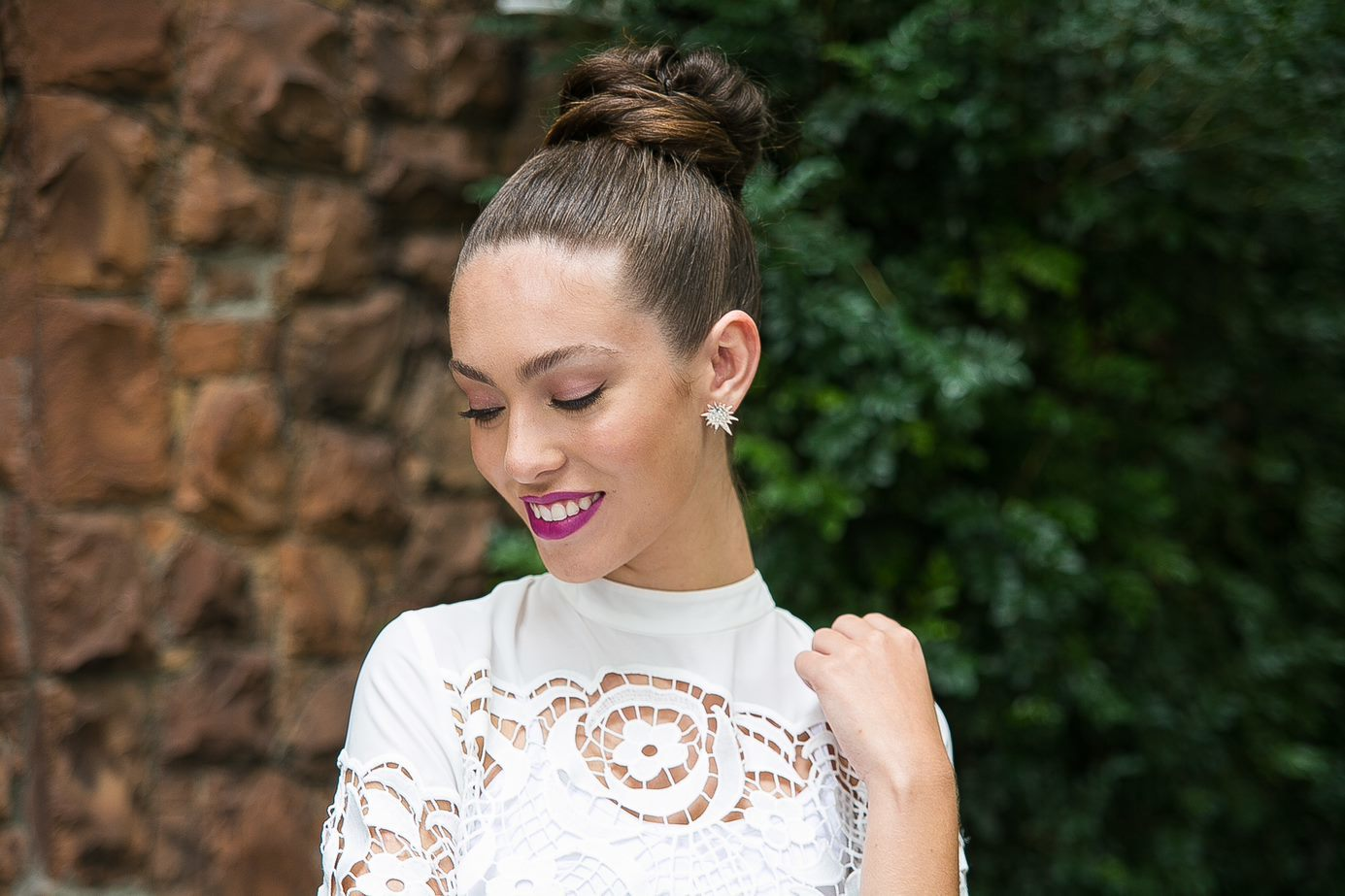 Wedding updos for long hair: Front facing shot of a bride with long honey brown hair styled into a sleek donut bun, wearing white dress and posing outside.