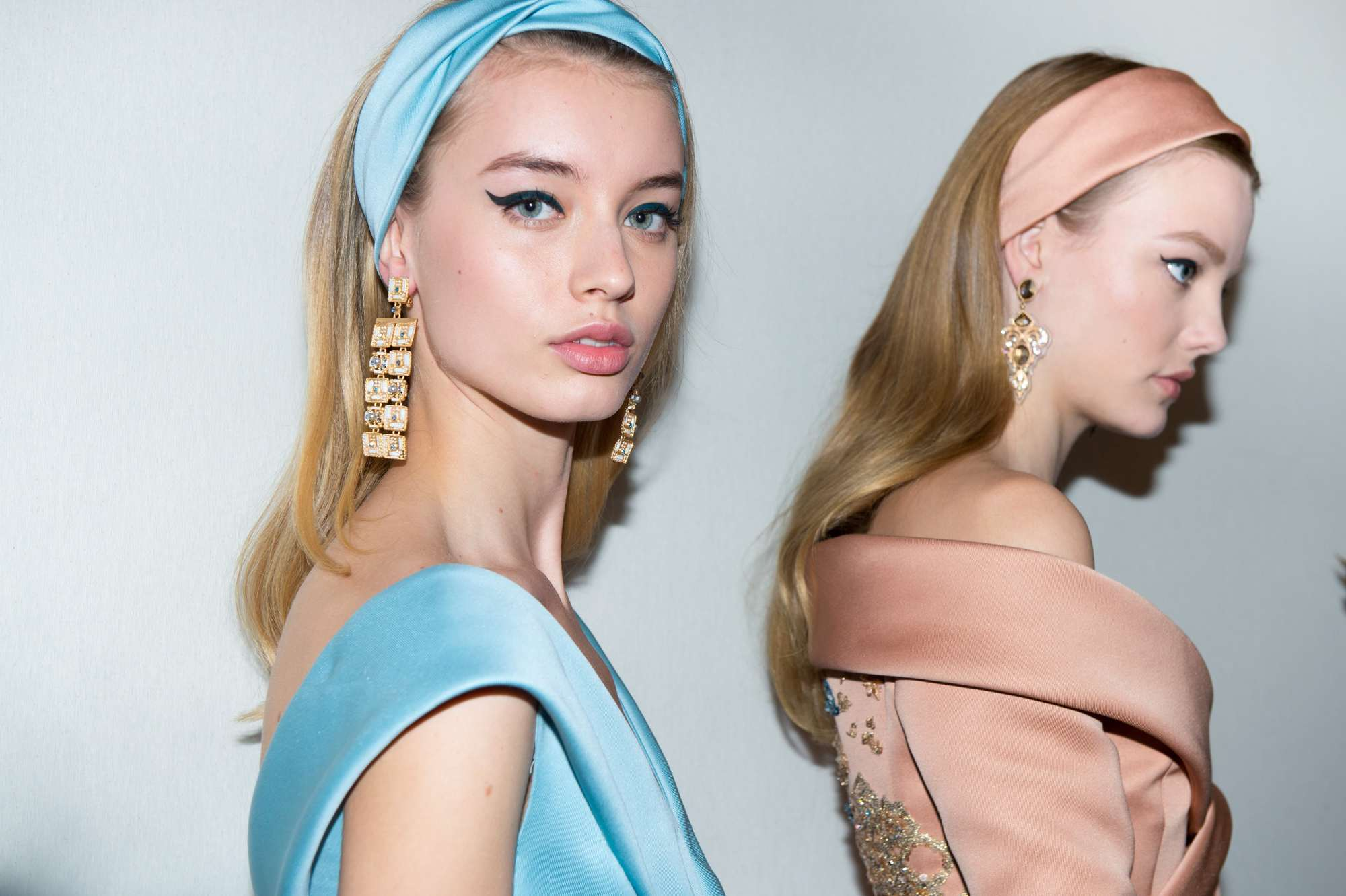 Headband and bandana hairstyles: Two models backstage at Elie Saab runway with golden blonde hair with loose waves wearing pastel coloured headband and dresses