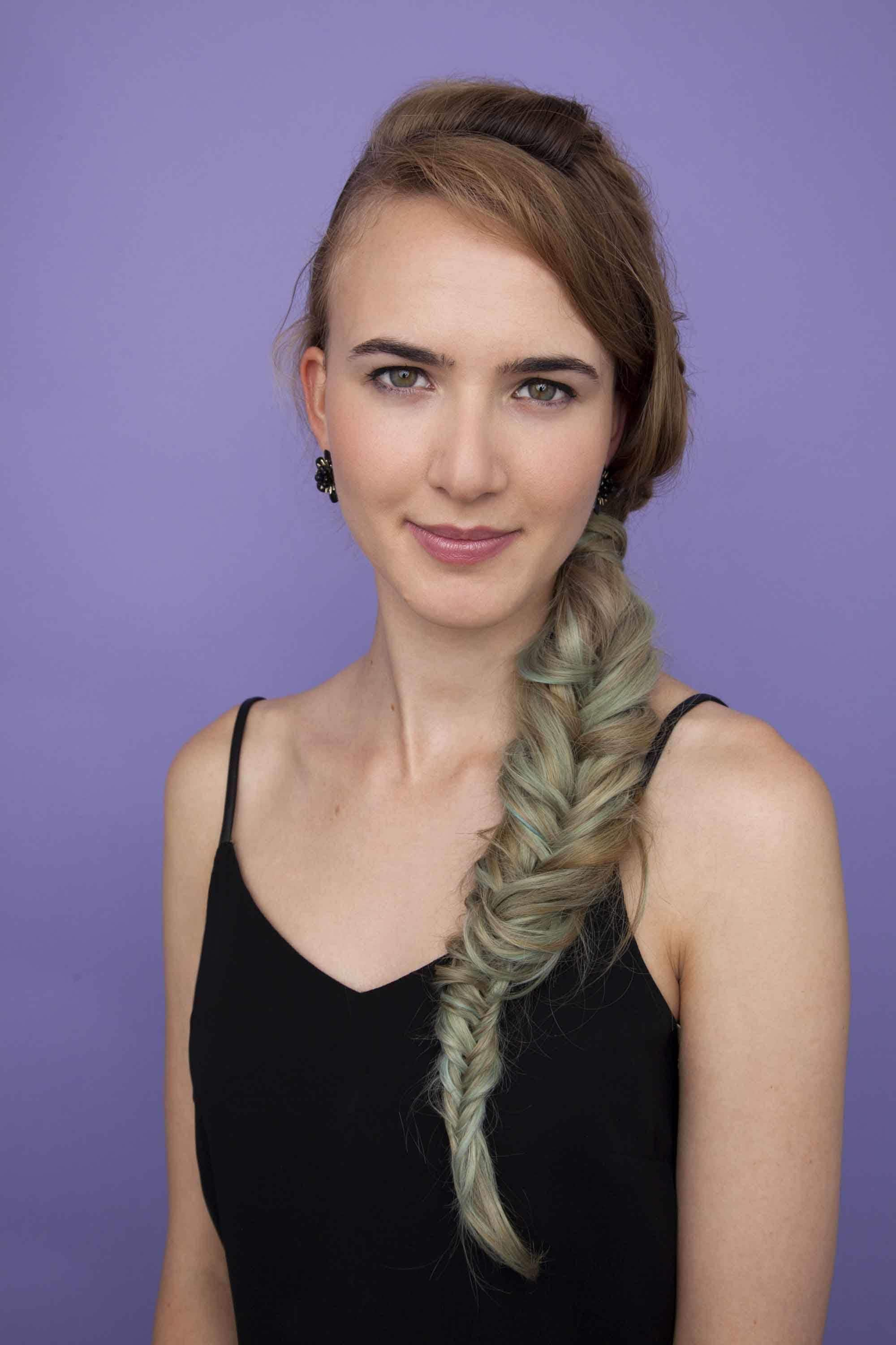 Festival hair: woman with long multi-coloured hair style dina side fishtail braid in studio setting