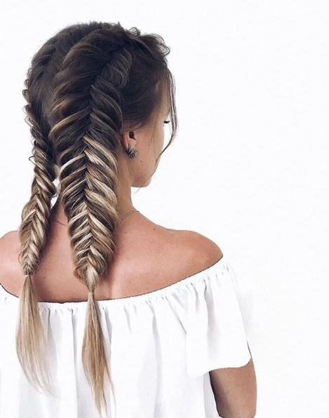 Boho hairstyles: Woman with brunette ombre hair in two fishtail plaits
