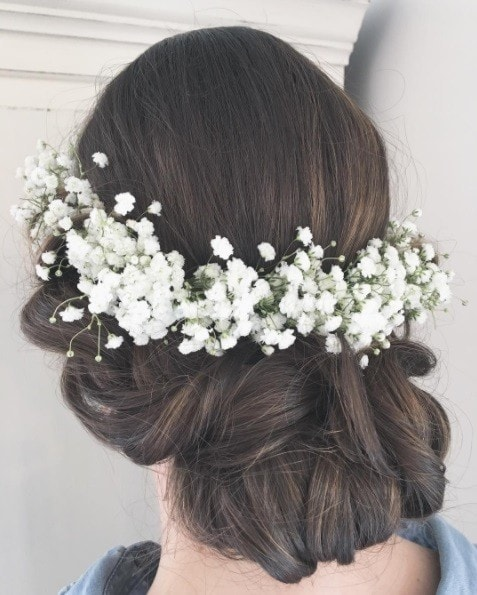 Wedding updos for long hair: Close up shot of a woman with long dark brown hair styled into an updo bridal style with a white flower crown.