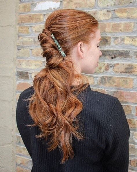 Curly prom hairstyles: Redhead girl with long curly hair in a french rolled ponytail with a hair clip accessory