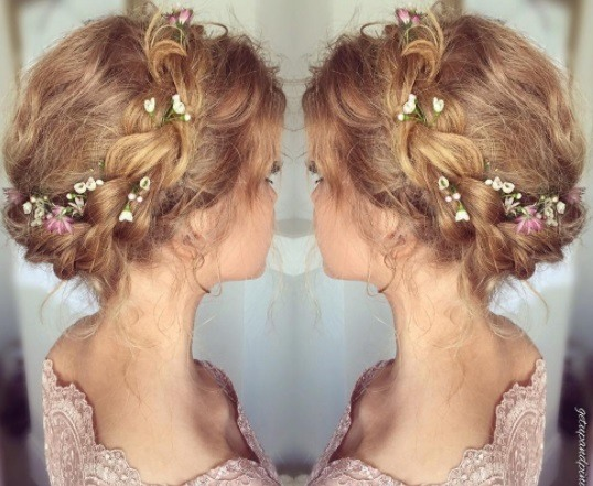 blonde woman with milkmaid braid with flowers in it