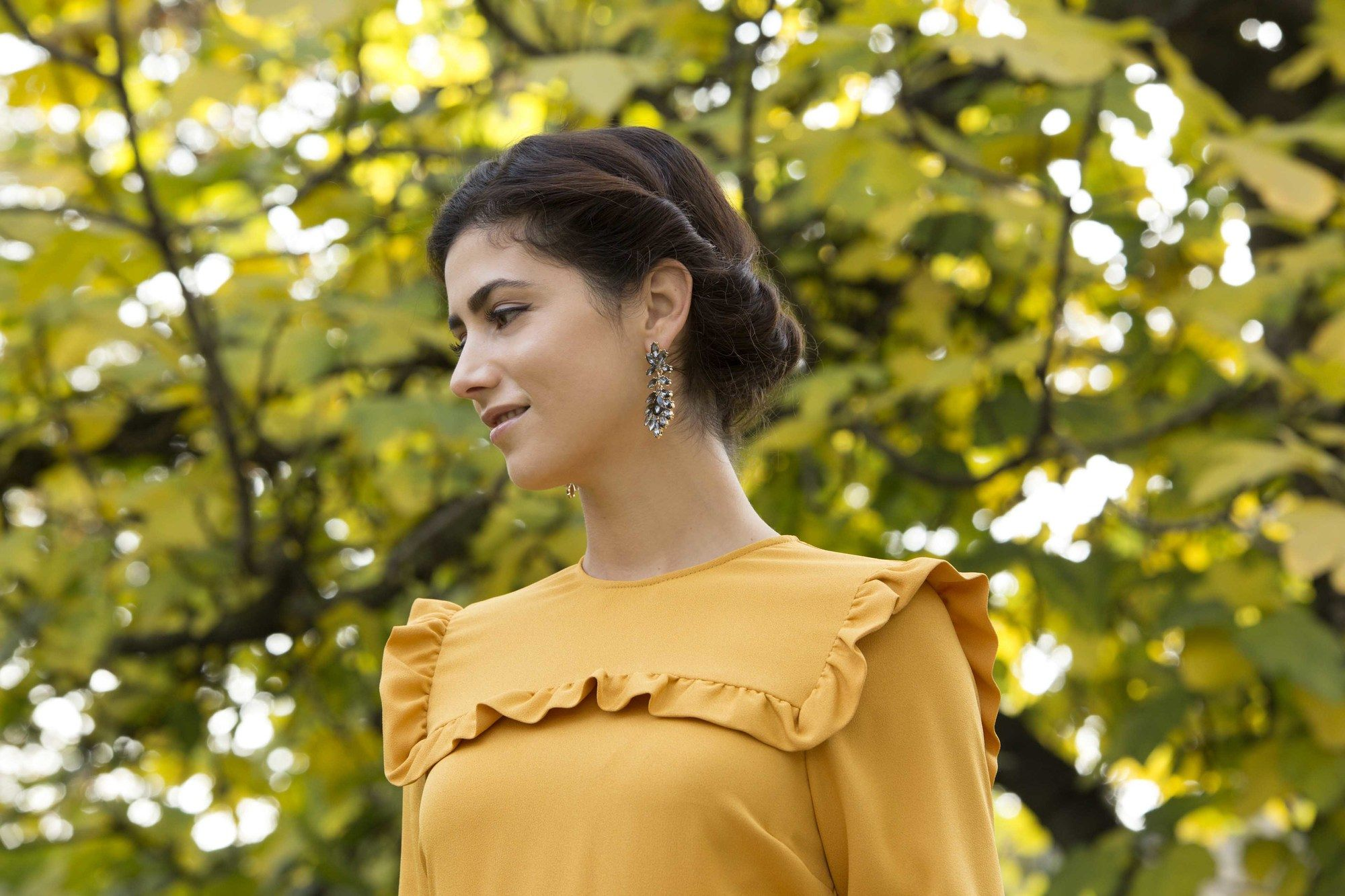 Wedding updos for long hair: Close up shot of a woman with long dark brown hair styled into a Gibson tuck hairstyle, wearing a yellow sundress and posing outside
