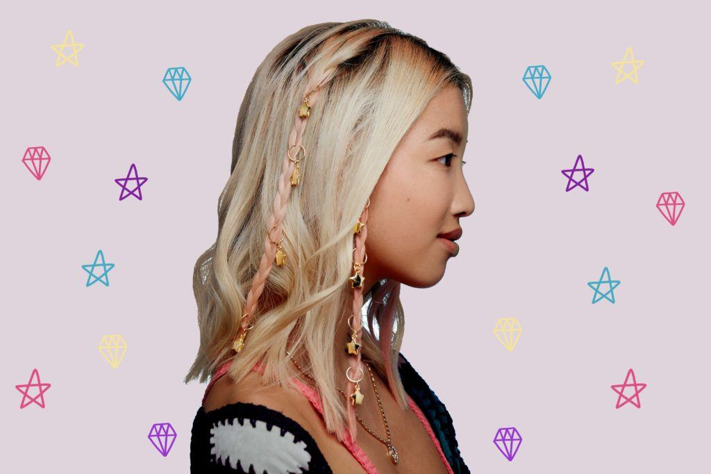 a young asian woman with blonde shoulder length hair with micro braids and hair rings