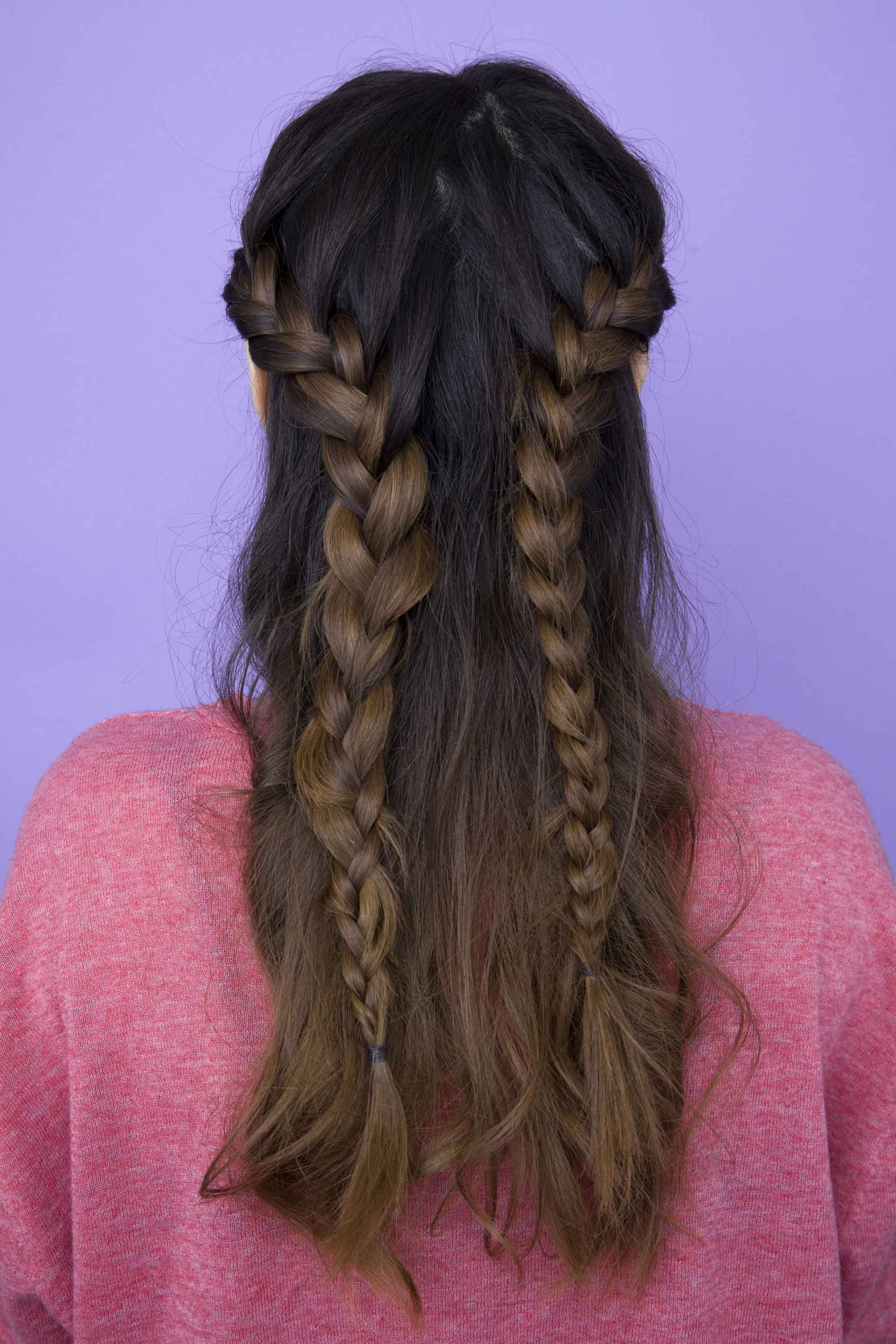 Festival hair: back view of woman with long brown hair styled with two french braids in half-up, half-down style. She is wearing a pink jumper and is in a studio setting with a purple background