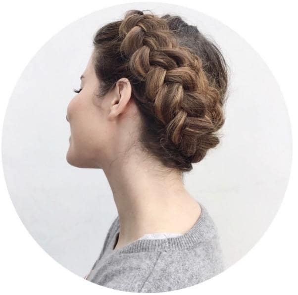 woman wearing grey with her brunette hair in a crown halo braid updo
